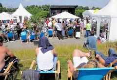 Fest am Spreehafen in Hamburg Wilhelmsburg - Zelte sind aufgestellt; ZuschauerInnen liegen in Liegestühlen auf dem Klütjenfelder Hauptdeich in der Sonne.