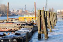 Holzdalben im Travehafen in Hamburg Steinwerder - Arbeitspontons und Arbeitsschiffe an den Dalben am Roeloffs Ufer. Im Hintergrund die Hamburger Innenstadt mit dem Turm der St. Michaeliskirche.