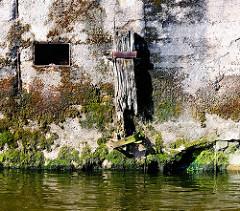 Verwitterter Holzpfahl mit Eisenhalterungen an einer Kaimauer im Hamburger Hafen - der Beton ist mit Moos und Algen bewachsen.