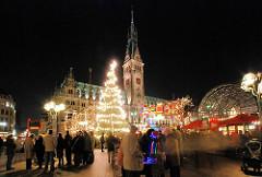 Weihnachtsmarkt in der Altstadt Hamburgs auf dem Rathausmarkt - ein Baum ist mit Lichtern geschmückt.
