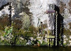 Verwitterter Holzdalben mit langer Kette im Hamburger Hafen - Kaimauer mit Moos und Wildpflanzen bewachsen.