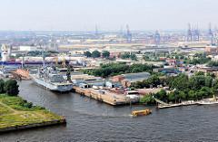 Blick auf Hamburg Steinwerder - ein Kriegsschiff liegt am Kai der Norderwerft im Reiherstieg - das Versorgungsschiff Berlin A 1411 liegt zur Reparatur im Hamburger Hafen. Auf der Norderelbe fährt eine gelbe Hafenfähre zum Anleger; im Hintergrund die