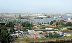 Kaianlagen beim Billhafen - Zollstation Zweibrückenstrasse - ein S-Bahnzug hat die Freihafenelbbrücke passiert und fährt Richtung Hauptbahnhof. An den Dalben liegen Frachtschiffe im Strom der Norderelbe.