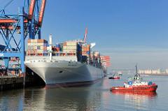Zwei rote Schlepper ziehen den Containerfrachter NYK HELIOS von der Kaimauer des Containerterminals Altenwerder. Das 2013 gebaute Frachtschiff hat eine Länge von 365,50m und eine Breite von 48,40m; der Frachter kann 13208 TEU Container transportieren