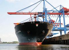 Bug mit Hamburg Wappen des 42m breiten Containerfrachters KYOTO EXPRESS unter den Containerbrücke von Hamburg Altenwerder.