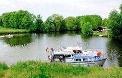 Blick auf die Dove-Elbe in Hamburg Curslack - zwei Sportboote liegen am Ufer; ein Motorboot fährt Richtung Bergedorf.