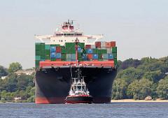 """Das 306m lange Containerschiff HATTA wird von einem Schlepper in den Hamburger Hafen geschleppt. Der 40m breite Frachter kann 6435 Standardcontainer TEU an Bord nehmen. Im Hintergrund der """"Alte Schwede"""" am Strand von Hamburg Othmarschen."""