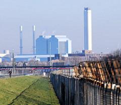 Zollzaun mit Stacheldraht an der Zollgrenze des Hamburger Freihafens am Klütjenfelder Deich in Hamburg Wilhelmsburg - im Hintergrund die Industriearchitektur des Hezkraftwerks Tiefstack in Hamburg Billbrook.