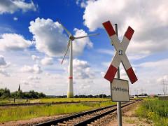 Bahnübergang und Andreaskreuz im Industriegebiet von Hamburg Altenwerder- lks. von der Windkraftanlage der Kirchturm der Kirche St. Gertrud.