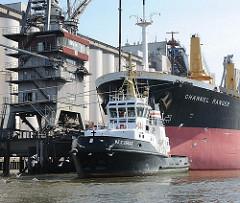 Schlepper ACCURAT und der Bug des Bulk Carriers CHANNEL RANGER; das  185m lange und 30m breite Frachtschiff hat seine Facht am Kai der Ölmühle gelöscht.
