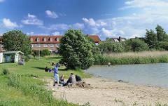 Badestrand am Allermöher See in Hamburg Neuallermöhe - im Hintergrund Wohnhäuser des Stadtteils.