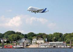 Ein Grossraumflugzeug Airbus Beluga fliegt über Hamburg Nienstedten zum Flugplatz des Airbusgeländes in Hamburg Finkenwerder. Eine Elbfähre liegt am Anleger Teufelsbrücke - am Elbufer Villen in Nienstedten.