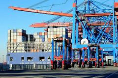 Das Frachtschiff CMA CGM CHRISTOPHE COLOMB hat am Burchardkai im Hamburger Hafen angelegt - die letze der Containerbrücken wird heruntergefahren - mehrer Portalhubwagen stehen bereit zum Abtransport der bald entladenen Container.
