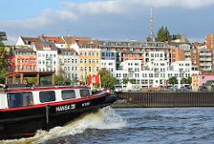Die bunten Häuser an der St. Pauli Hafenstrasse - eine Barkasse mit Hamburg Fahne auf der Elbe.