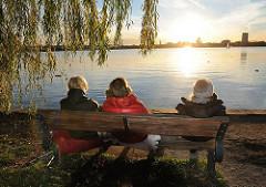 Herbst an der Alster - Hamburgerinnen geniessen die untergehende Sonne auf einer Bank an der Alster im Hamburger Stadtteil Uhlenhorst.
