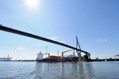Köhlbrandbrücke über die Süderelbe - ein Containerschiff fährt unter der Brücke Richtung Elbe.