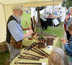 Biohof Gut Wulksfelde - Bauernmarkt. Aussteller präsentieren ihre Bioprodukte und Kunsthandwerk.  Der Hersteller von Bambusflöten zeigt seine selbstgefertigten Instrumente den ZuschauerInnen.