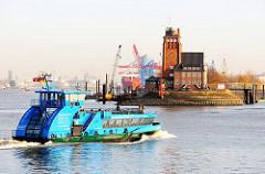 Eine Hamburger Hafenfähre läuft den Finkenwerder Anleger an - im Hintergrund das von dem Hamburger Oberbaudirektor Fritz Schumacher entworfene Lotsengebäude sowie Containerbrücken des Terminals Burchardkai.