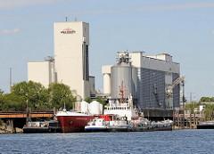 Industriegebäude am Reiherstieg im Hamburger Stadtteil Wilhelmsburg - Schiffe liegen am Ufer des Hamburger Wasserwegs.