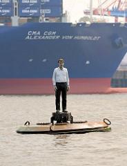 """Skulptur """"Mann auf Boje"""" Elbe, Hamburger Hafen - Künstler Stephan Balkenhol - im Hintergrund der Containerfrachter CMA CGM ALEXANDER VON HUMBOLDT."""