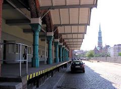Rampe mit historischen Säulen am Zollamt Teerhof in der Hamburger Speicherstadt am Zollkanal - der Boden ist mit Pflastersteinen gepflastert - im Hintergrund der Zollzaun am Kanal und die Hamburger St. Katharinenkirche.
