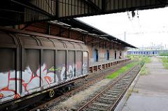 Güterwaggons am Bahnsteig - im Hintergrund fährt ein Zug der Metronom Richtung Hamburg Hauptbahnhof - Bilder aus dem Stadtteil Hamburg-Hafencity.