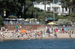 Cafe und Restaurant am Elbufer - Gäste sitzen unter Sonnenschirmen mit Blick auf die Elbe und das Leben am Elbstrand