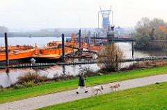 Saugerstation der HPA mit Schuten am Finkenwerder Vorhafen - im Hintergrund die Krananlage der Hamburger Aluminiumwerke.