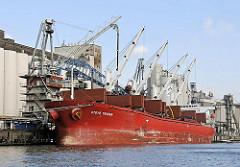 Das Frachtschiff Stove Trader beim Löschen der Ladung am Neuhöfer Kanal / Süderelbe. Der Frachter hat eigene Ladekräne an Bord, sodass die Ladung auch ohne Kaikräne gelöscht werden kann.