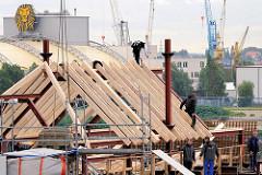 Setzen des Dachfirst - Restaurierung der St. Pauli Landungsbrücken - Zimmerleute arbeiten auf dem Dach und nageln die Dachbalken fest. Im Hintergrund das Zelt vom Musical König der Löwen.