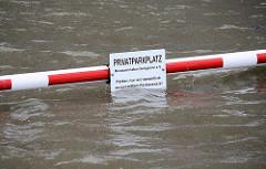 Hinweisschild Privatparkplatz - Hochwasser beim Museumshafen von Hamburg Oevelgönne.