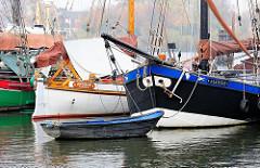 Schiffsbug und Ruderboot, historische Fischerboote im Hafen von Hamburg Finkenwerder.