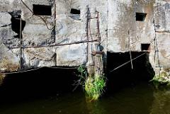 Kaimauer aus Beton mit Stahlarmierung im Hamburger Hafen, alter Holzbalken mit Gras.