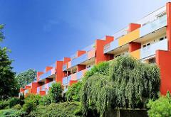 Neubauten im Grünen - bunter Balkonanstrich eines mehrstöckigen Wohnhauses - grüne Sträucher und Trauerbuche.