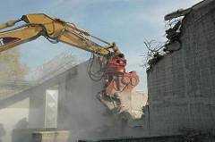 Einreissen der Gefängnismauer - Abriss der JVA Neuengamme - ein Abrissbagger  reisst die Gefängnismauer der JVA Neuengamme nieder.