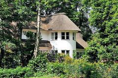 Wohngebäude mit weisser Putzfassade und Reetdach zwischen Bäumen in Hamburg Blankenese.