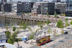Blick über die Marco Polo Terrassen - moderne Neubauten am Grasbrookhafen - Doppeldeckerbus der Hamburger Stadtrundfahrt an einer Haltestelle.
