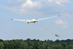 Start eines Segelflugzeug auf dem Boberger Segelflugplatz in Hamburg Lohbrügge; das Flugzeug wird von einer Winde hochgezogen und schwebt schon über den Bäumen der Boberger Niederung.