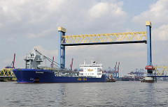 Angehobene Hubbrücke am Kattwykdamm - ein Frachtschiff hat fährt auf der Süderelbe - im Hintergrund die Containerkräne des Terminals Altenwerder.