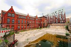 Baustelle vor dem ehem. Gebäude des Amts für Strom- und Hafenbau in der Hamburger Hafencity - im Hintergrund moderne Architektur.