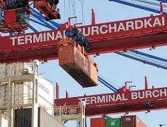 Ein Container hängt an der Containerkatze unter der Containerbrücke der Terminal Burchardkai und wird an Land transportiert. Fotos aus dem Hamburger Hafen - Bilder aus der Hansestadt Hamburg.