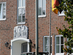 Kasernengebäude - Skulpturenschmuck über dem Gebäudeeingang - Deuschlandfahne am Fahnenmast.