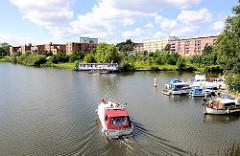 Blick über die Bille zu Wohnblocks in Hamburg Hamm - moderne Neubauten am Wasser, ein Hausboot / Wohnschiff liegt am Ufer; ein Motorboot fährt auf der Bille, weitere Sportboote liege im Sportboothafen.