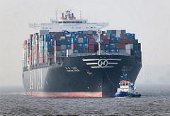 Der Containerfrachter HANJIN SPAIN  fährt mit Schlepperhilfe in den Hamburger Hafen ein - hoch beladener Containerfrachter vor Hamburg.