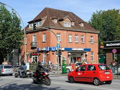 Historisches Bahnhofsgebäude Hochbahnhaltestelle Farmsen - Backsteinarchitektur. Strassenverkehr mit Motorrad und Quad auf der Hauptverkehrsstrasse.
