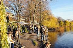 Herbstabend am Alsterufer in Hamburg Uhlenhorst - Gäste des kleinen Cafes Alsterperle am Ufer der Aussenalster. Sie sitzen am Wasser auf Bänken oder an Tischen. Die Herbstsonne beleuchtet golden die Bäume am Ufer des Hamburger Sees.