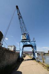 Der blaue Hafenkran am Billhafen in Hamburg Rothenburgsort wird auf Schienen entlang der Kaianlage bewegt. Im Hintergrund die Eisenbahnbrücke über den Oberhafenkanal / Billehafen.