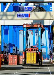 Der Portalhubwagen hat einen der Container aufgenommen und fährt ihn an seinen Lagerplatz - Bilder vom HHLA Container Terminal Burchardkai / Athabaskakai.