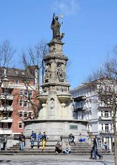 Hansaplatz in Hamburg St. Georg - Hansabrunnen mit Hansskulptur; Menschen in der Sonne am Brunnen.