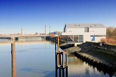 """Ufer am Müggenburger Zollhafen - rechts das Haus der Projekte """"die Mügge"""" - das Gebäude ist eine Stadtteilwerkstatt. Im Hintergrund die Autobahnbrücke und Gewerbe / Schornsteine auf der Peute."""